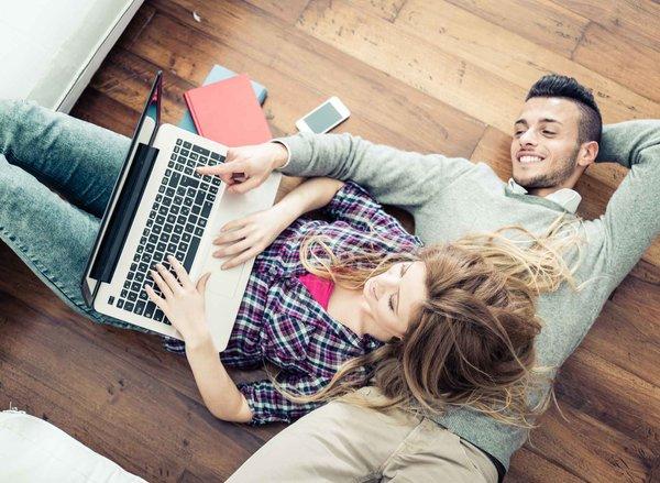 glückliches Paar, das am Boden liegt und sich etwas auf dem Laptop ansieht