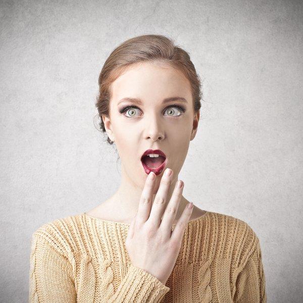 schockierte Frau vor grauem Hintergrund