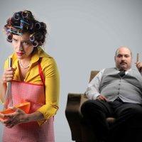 Frau mit Kochschürze und Locken im Haar mit Mann der auf Stuhl sitzt