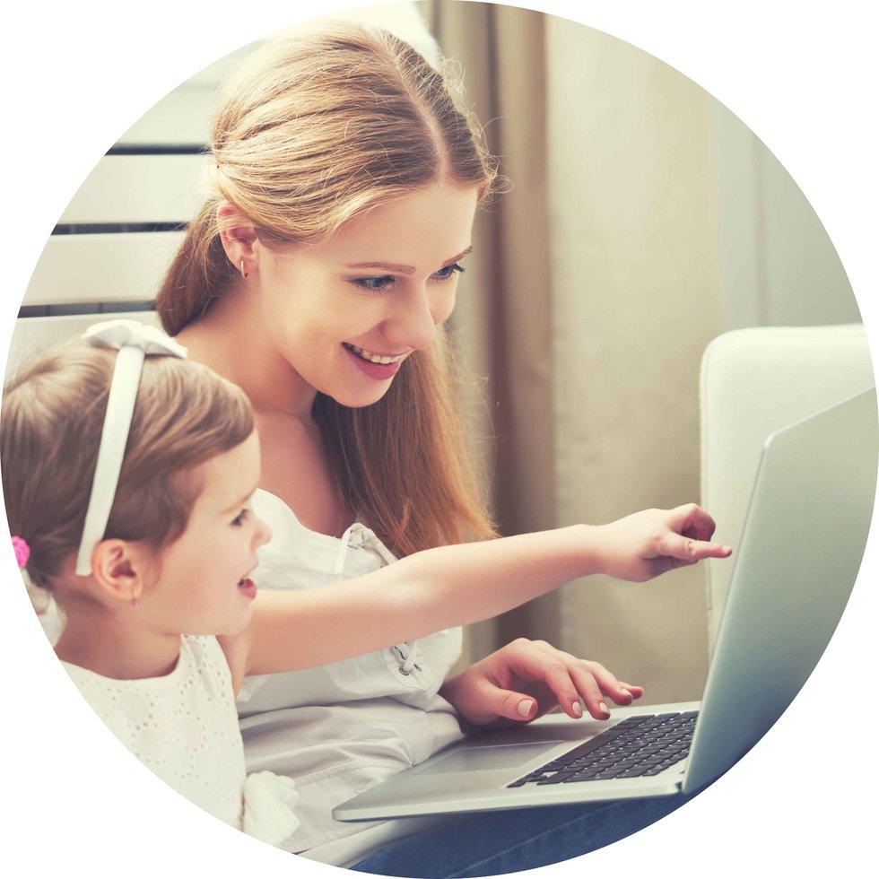 Frau mit Kleinkind, welches mit Finger auf einen Laptop zeigt